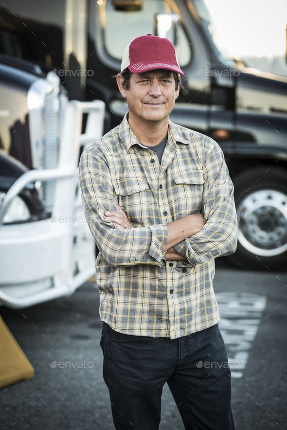 Caucasian man truck driver with his truck parked in a lot at a truck stop. - Stock Photo - Images