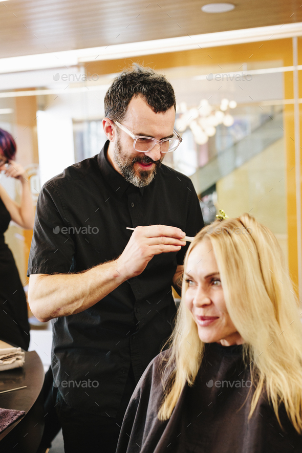 A hair colourist, a man using a paintbrush to cover sections of a woman's blonde hair. - Stock Photo - Images