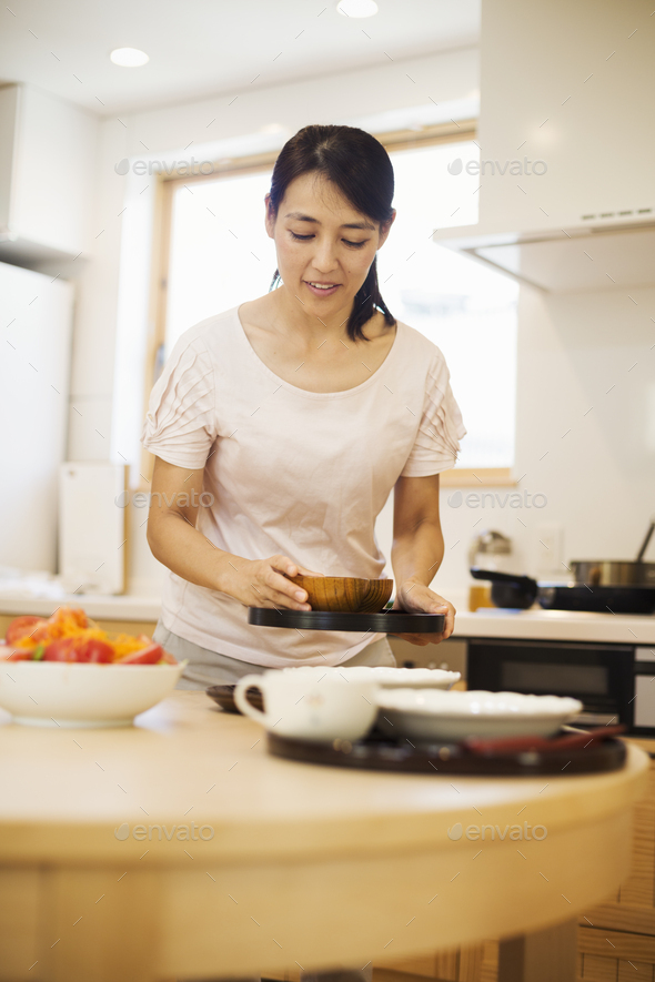 Family home. A woman preparing a meal arranging dishes on a table. - Stock Photo - Images