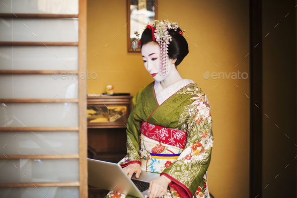 A woman dressed in the traditional geisha style, wearing a kimono and obi, with an elaborate - Stock Photo - Images