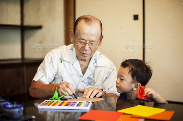 Japanese man and little boy sitting at a table, making Origami animals using brightly coloured - Stock Photo - Images