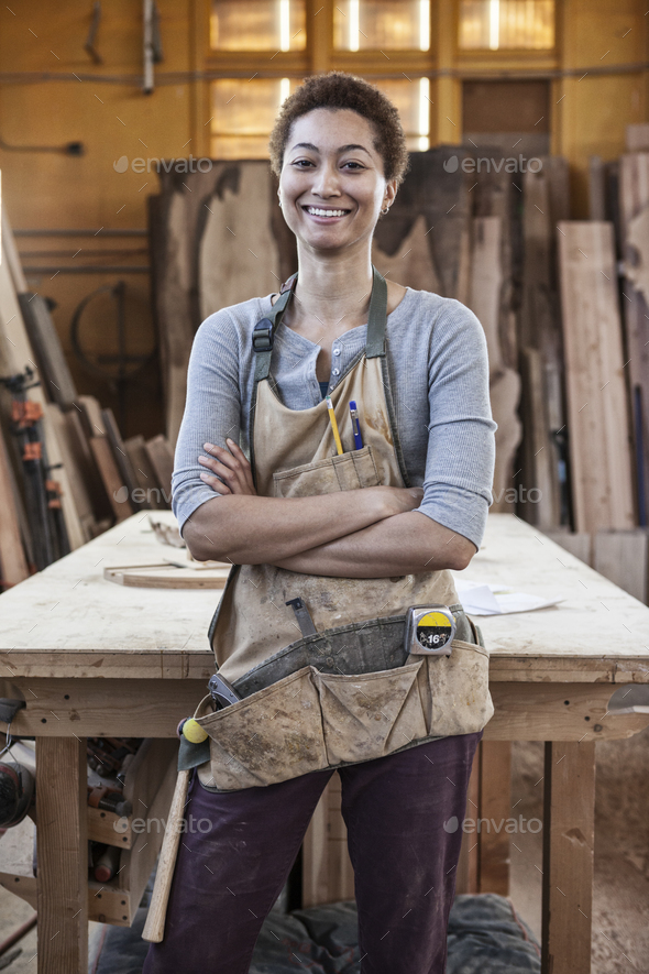 A black woman factory worker wearing an apron standing next to a work station in a woodworking - Stock Photo - Images