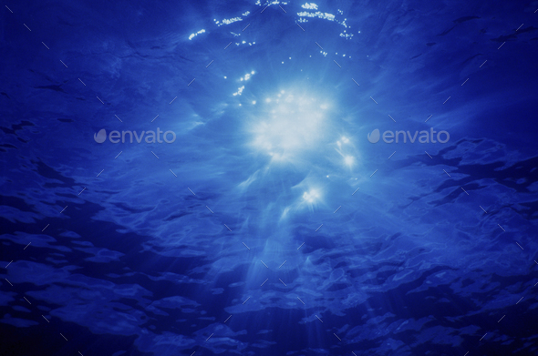 Brilliant Crepuscular rays and a sunburst shining through moving water, view from below the surface. - Stock Photo - Images