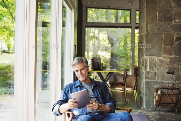 A man seated by a window reading using a digital tablet. - Stock Photo - Images