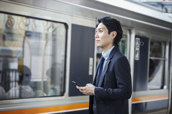 Businessman wearing suit standing at train station platform, holding mobile phone. - Stock Photo - Images