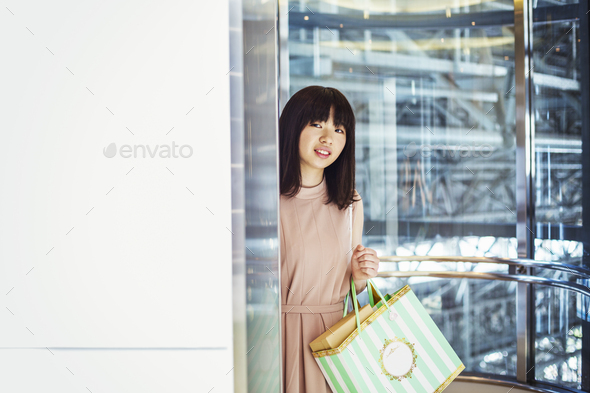 Young woman with long brown hair in a shopping centre, carrying shopping bags. - Stock Photo - Images