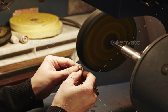 A person holding a small ring and using a grinding machine to shape and polish it. Workbench in a - Stock Photo - Images
