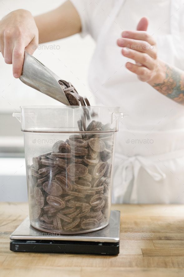 Close up of a woman wearing a white apron standing at a work counter in a bakery, weighing - Stock Photo - Images
