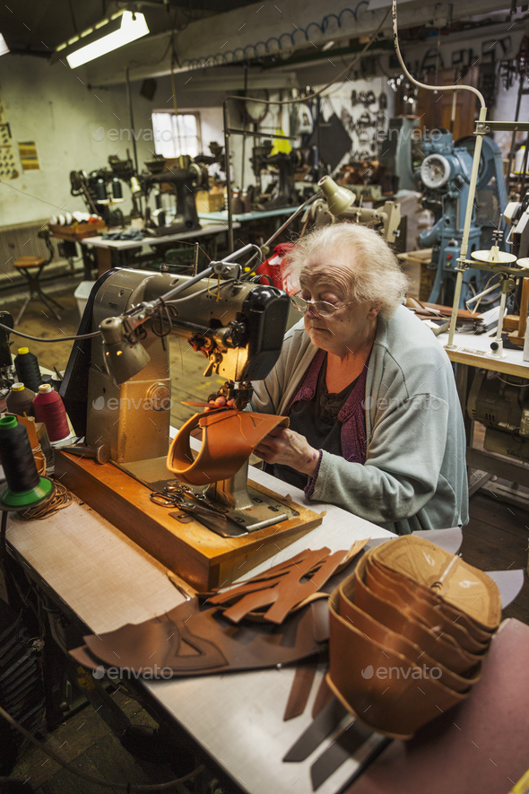 Older woman sitting at a sewing machine in a shoemaker's workshop. - Stock Photo - Images