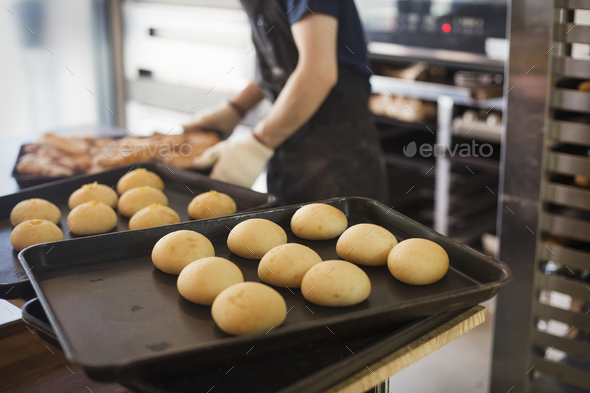 Person working in a bakery, placing freshly baked rolls on large trays. - Stock Photo - Images