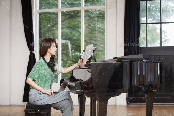 Young woman sitting at a grand piano in a rehearsal studio, annotating sheet music. - Stock Photo - Images
