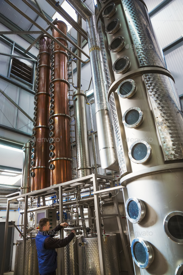 Tall copper distillery chambers in a brewery, brewing storage tanks in copper and steel. A man in - Stock Photo - Images