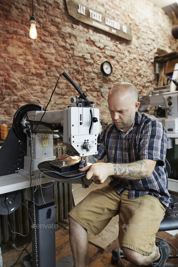 A leather worker, craftsman using an industrial sewing machine on leather material, making a bag. - Stock Photo - Images