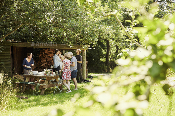 A group of men and women around a lunch table in summer in the shade of trees in a garden. - Stock Photo - Images