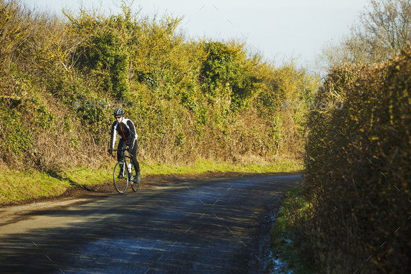 A cyclist riding along a country road on a clear sunny winter day. - Stock Photo - Images