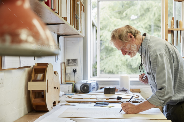 A violin maker at his drawing board drawing out the plans and outline for a new instrument. - Stock Photo - Images