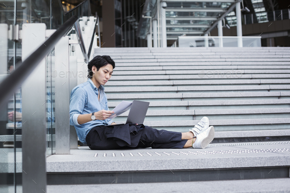 Businessman wearing blue shirt sitting outdoors on steps, holding papers, laptop on his knees. - Stock Photo - Images