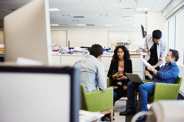 A woman and three men, a team sitting and standing in an office talking to each other. - Stock Photo - Images