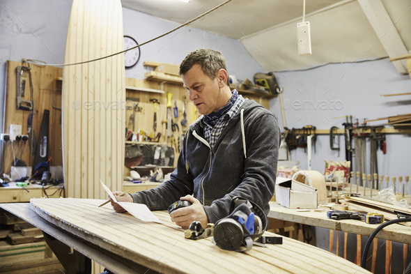 Man standing in a workshop with a wooden surf board, holding paper and pen. - Stock Photo - Images