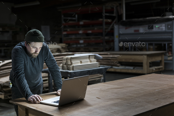 A Caucasian carpenter working on his lap top after hours in a large woodworking factory. - Stock Photo - Images