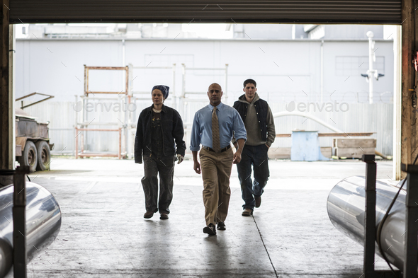 Workers and management person walking through a door into a sheet metal factory. - Stock Photo - Images