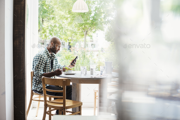 Man wearing a checked shirt sitting in a cafe, using his mobile phone. - Stock Photo - Images