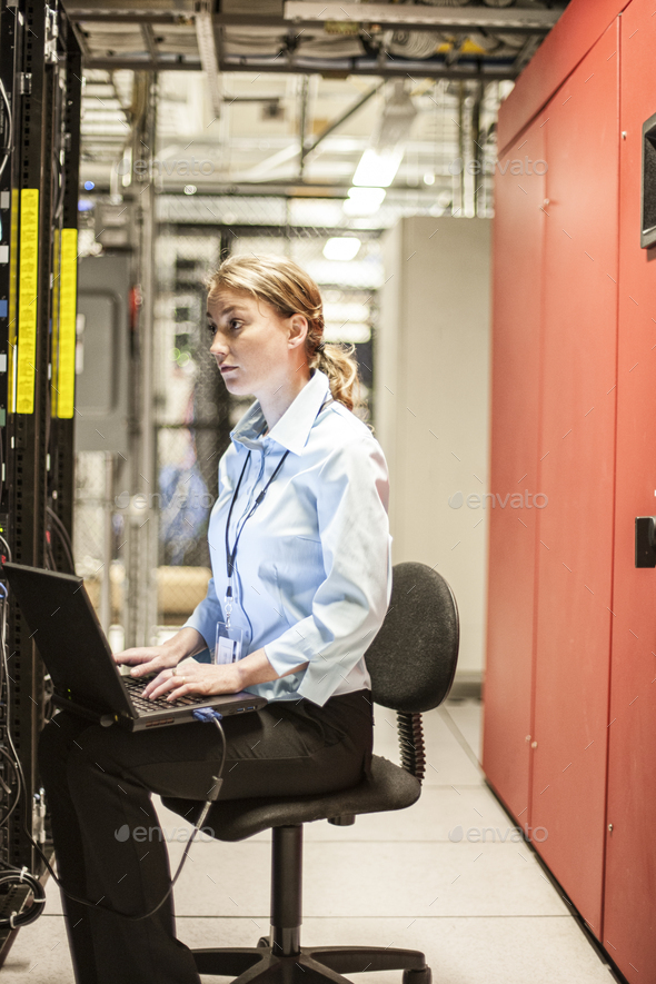 Caucasian woman technician working on computer servers in a server farm. - Stock Photo - Images
