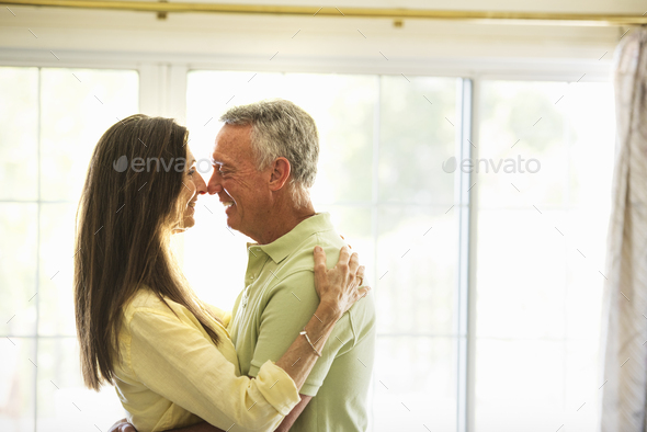 Senior couple standing indoors, embracing. - Stock Photo - Images