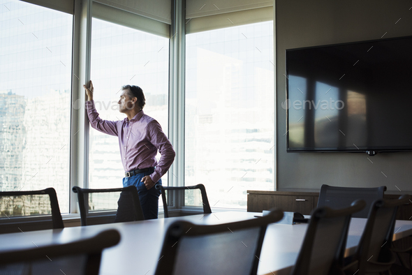 A man in a meeting room looking out of a window at an urban landscape. - Stock Photo - Images