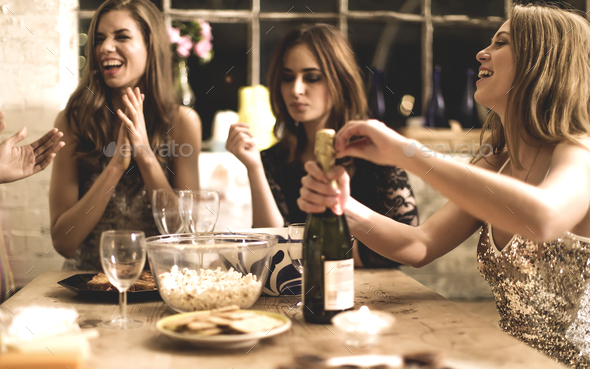 A group of women at a party, pouring and drinking champagne. - Stock Photo - Images