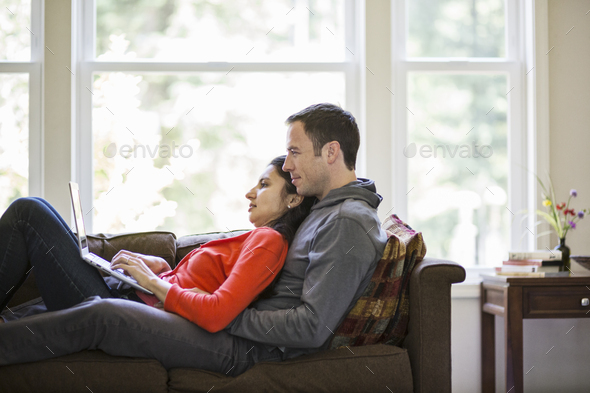 Caucasian man and mixed race caucasian woman using a laptop computer while sitting on a couch in - Stock Photo - Images