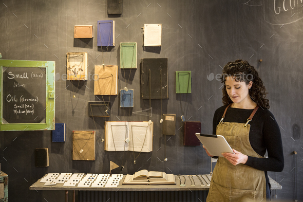 Woman with curly brown hair wearing apron standing in her pottery shop, looking at digital tablet, - Stock Photo - Images