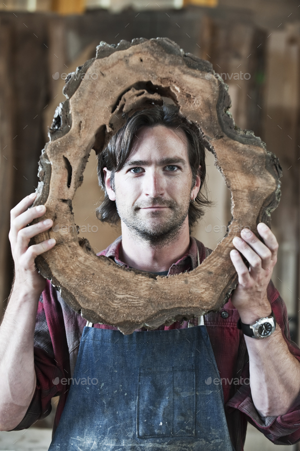 Caucasian man factory worker holding a cut piece from a section of a reclaimed recycled tree in a - Stock Photo - Images