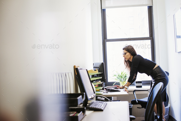 A young woman standing at a desk looking at a computer screen. - Stock Photo - Images