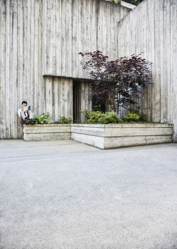 Businessman taking a break in a city park alcove. - Stock Photo - Images