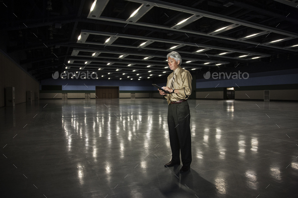 An Asian businessman standing in a dimly lit and dark exhibition area in a convention center. - Stock Photo - Images