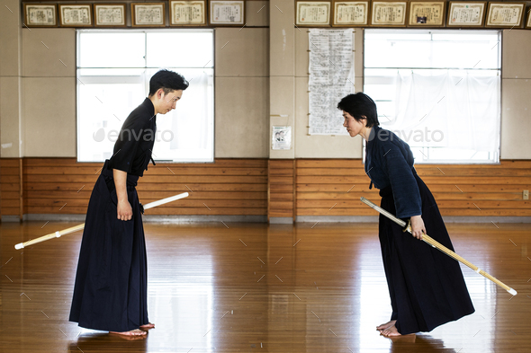 Female and male Japanese Kendo fighters standing opposite each other on wooden floor, bowing and - Stock Photo - Images