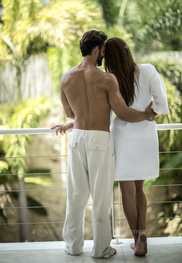 A rear view of a couple standing on a balcony hugging. - Stock Photo - Images