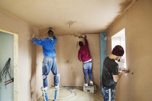 Three men, two plasterers wearing stilts smoothing fresh plaster high up on the walls of a house - Stock Photo - Images