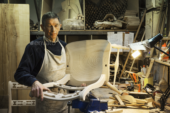Man standing at a work bench in a carpentry workshop, working on a wooden chair. - Stock Photo - Images