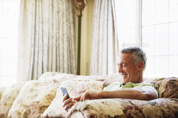 Smiling senior man sitting on a sofa, using a mobile phone. - Stock Photo - Images