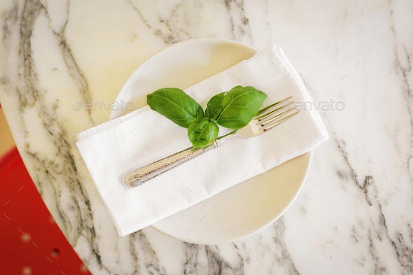 A marble tabletop and napkin with herb basil. - Stock Photo - Images