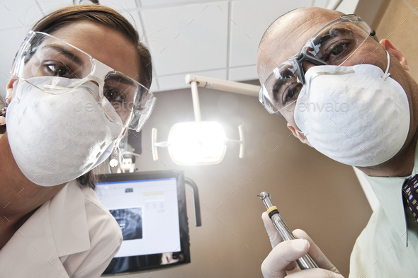 Looking up at a male dentist and a female technician from the viewpoint of a patient. - Stock Photo - Images