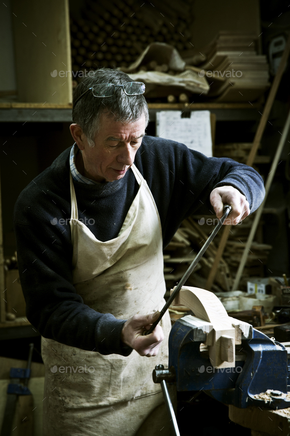 A man working in a furniture maker's workshop using a rasp on a wooden shape in a clamp. - Stock Photo - Images