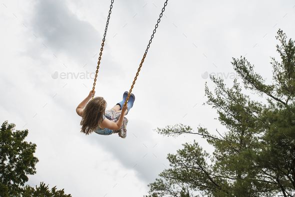 A girl on a rope swing, high in the air - Stock Photo - Images
