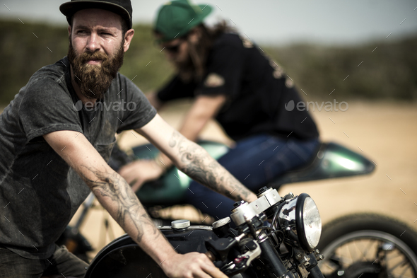 Side view of bearded man with tattoos on his arm sitting on cafe racer motorcycle on a dusty dirt - Stock Photo - Images