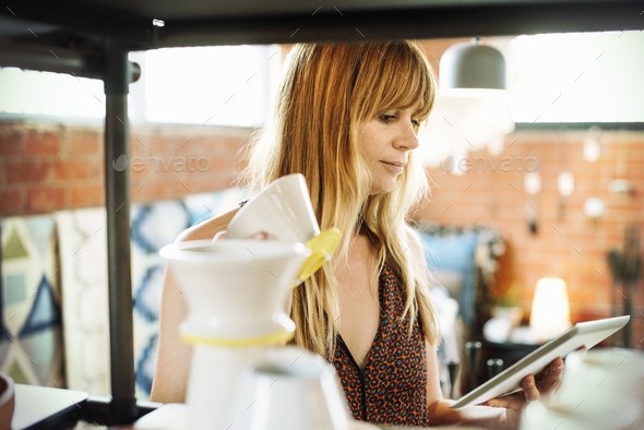 Woman in a shop, holding a digital tablet and small ceramic pot. - Stock Photo - Images