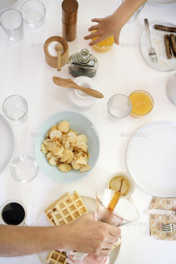 High angle view of a breakfast table, waffles, fried pototoes, coffee and juice. - Stock Photo - Images