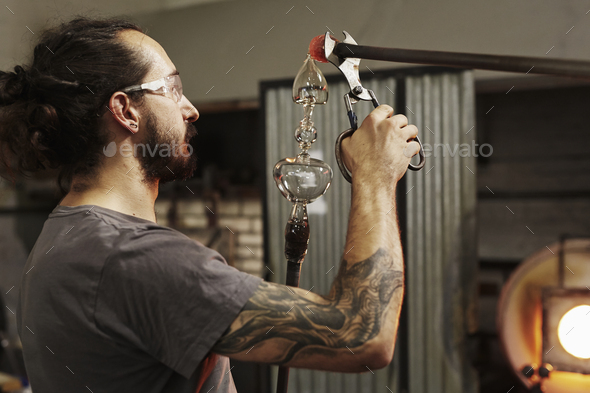 A glassblower with pliers working on a piece of glass. - Stock Photo - Images