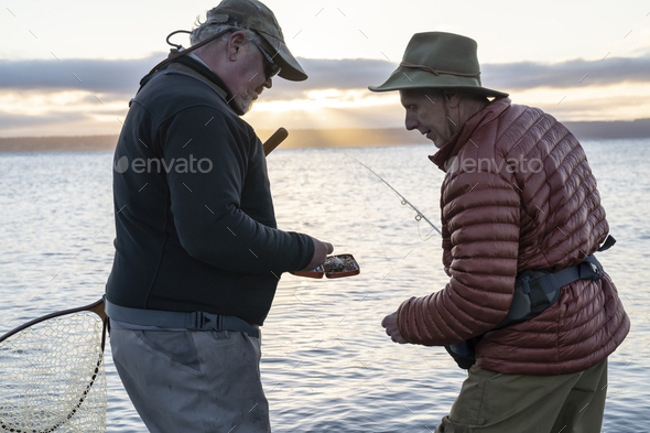 A male fly fisherman watches his guide work putting on a new fly to try for salmon or trout at a - Stock Photo - Images